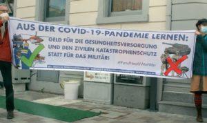 """Banner mit dem Text """"Aus der Covid-19-Pandemie lernen: Geld für die Gesundheitsversorgung und den zivilen Katastrophenschutz statt für das Militär!"""""""